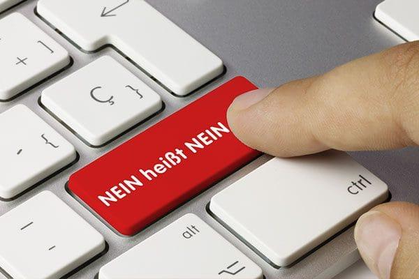 """Hier ist ein Foto. Darauf sieht man einen Ausschnitt einer hellgrauen Tastatur. Eine Taste ist rot und darauf steht: """"NEIN heißt NEIN"""". Ein Finger ist im Bild zu sehen. Es sieht aus, als wolle jemand diese rote Taste drücken."""