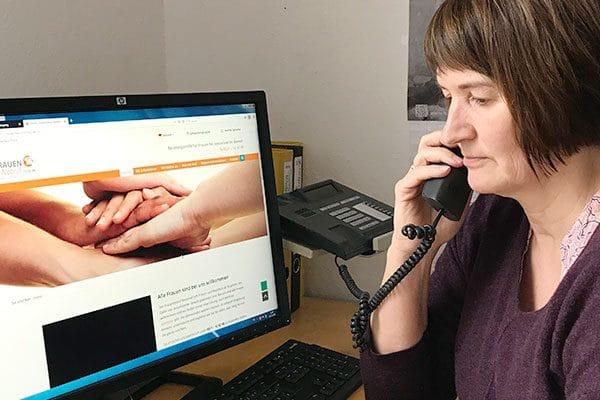 Hier ist ein Foto. Darauf sieht man rechts im Bild eine Frau mit Telefon-Hörer am Ohr. Links im Bild einen PC-Monitor und eine Tastatur. Das ist im Telefon-Büro vom Frauennotruf Bielefeld e.V. So sieht es aus, wenn eine Mitarbeiterin Telefon-Beratung macht.