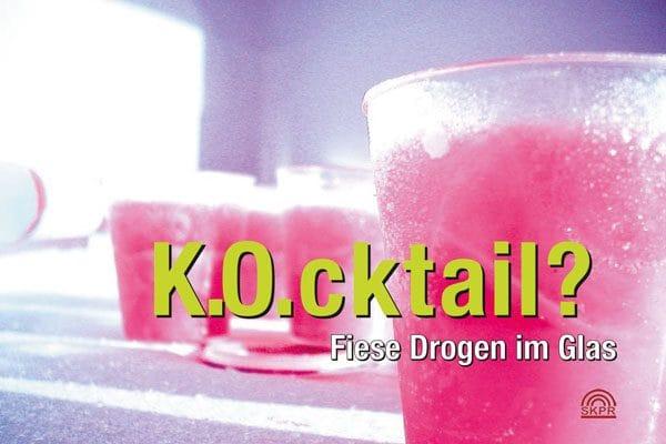 """Hier ist ein Foto. Darauf sieht man auf lila Hintergrund mehrere durchsichtige Plastik-Becher, gefüllt mit rosa Getränken. In großen leuchtend-grünen Buchstaben steht mittig """"K.O.cktail?"""". Darunter kleiner in weißer Schrift """"Fiese Drogen im Glas"""". Unten rechts ist noch das Logo vom """"SKPR"""" (Sozial- und kriminal-präventiver Rat der Stadt Bielefeld, der den Druck der Karten finanziert hat."""