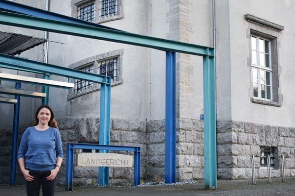 """Hier ist ein Foto. Darauf sieht man unten rechts im Bild eine Frau, die in die Kamera lächelt. Hinter ihr sieht man die Eingangssituation vom Landgericht Bielefeld: blaue Metall-Bögen, ein Stein-Schild mit der Aufschrift """"LANDGERICHT"""" und einen Teil vom alten Teil des Gerichts-Gebäudes."""