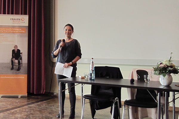 Hier ist ein Foto. Darauf sieht man links einen Aufsteller vom Frauennotruf Bielefeld. Etwa mittig steht eine Frau mit Zetteln in der Hand, die in ein Mikrofon spricht. Rechts im Bild sind zwei Tische mit Stühlen dran, Wasserflaschen und Gläser auf den Tischen und eine Vase mit einem Blumenstrauß.