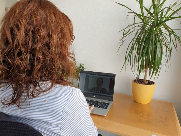 Hier ist ein Foto. Das Foto zeigt den Hinterkopf einer Frau. Sie schaut auf einen Laptop. Der Bildschirm zeigt eine Beraterin.